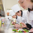 Stock Photo: Chef finishing her salad in culinary class