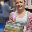 Woman leaning at a bookshelf holding books — Stock Photo #23100318