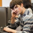 Student looking tired in computer room — Stock Photo