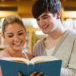 Couple standing holding a book in the library — Stock Photo