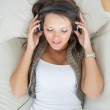 Calm woman lying on the sofa and listening music — Stock Photo #23100522