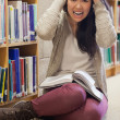 Stressed student sitting on library floor — Stock Photo