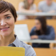 Teacher standing at the lecture hall smiling — Stock Photo