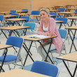 Student sitting at desk in empty exam hall — Stock Photo #23100656