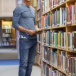 Student standing at a bookshelf smiling holding a tablet pc — Stock Photo #23100660