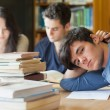 Tired student resting in library — Stockfoto