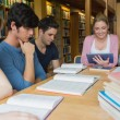 Stock Photo: Students studying together in library with one using a tablet pc