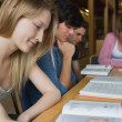 Students studying around library table — Stock Photo