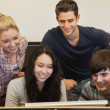 Students sitting standing looking at computer — Stock Photo