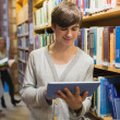 Student using tablet pc standing in library — Stock Photo