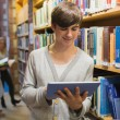 Stock Photo: Student using tablet pc standing in library