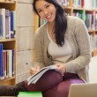 Smiling student working on library floor — Stock Photo