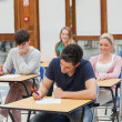 Students sitting at the exam room writing — Stock Photo #23101126