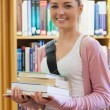 Woman smiling holding books — Stock Photo #23101138