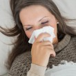 Sick woman lying on sofa and blowing nose — Stock Photo