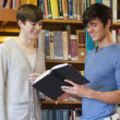 Students standing in library looking at book — Stock Photo #23101156
