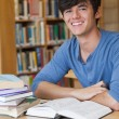 Student sitting at desk while smiling — Stock Photo #23101204