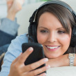 Woman using her smartphone and listening to music — Stock Photo