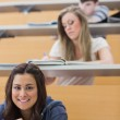 Student sitting reading a book in lecture hall — Stock Photo