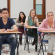 Students sitting at the classroom listening  — Photo