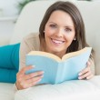 Happy women reading a book and lying on the sofa — Stock Photo #23101578