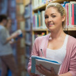 Student leaning at the bookshelf — Stock Photo
