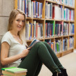 Stock Photo: Girl sitting on the library floor holding a book