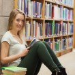 Girl sitting on the library floor holding a book — Stock Photo