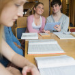 Happy students with tablet pc in library — Stock Photo