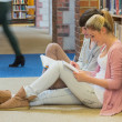 Students sitting in front of a bookshelf — Stock Photo #23101874