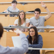 Students sitting at the lecture hall with man razing hand to ask — Stock Photo #23101918