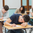 Man sleeping in exam hall — Stock Photo