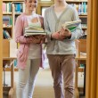 Couple standing at the library holding books — Stock Photo #23102152