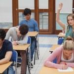 Woman raising hand during exam — Stock Photo
