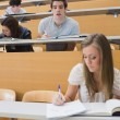 Student looking at another's work in lecture hall - Stock Photo