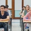 Students looking up in exam hall — Stock Photo