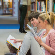 Students sitting on floor of library and studying — Stock Photo