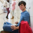 Man sitting on the floor at the hallway smiling — Stock Photo