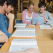 Students in the library studying with two using tablet pc — Stockfoto