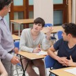 Stock Photo: Students sitting talking to teacher