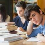 estudiante apoyado en la mesa buscando cansado — Foto de Stock