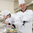 图库照片: Happy chef with others preparing salads
