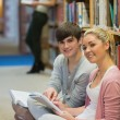 Man and woman sitting in front of a bookshelf while smiling  — Stock Photo