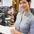 Teacher standing at the computer room holding papers — Stock Photo #23103878