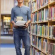 Man standing at a bookshelf holding a pile of books — Stock Photo