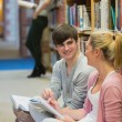 Students sitting in front of a bookshelf — Stock Photo