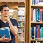 Student standing at the bookshelf thinking — Stock Photo #23104356