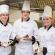 Three happy Chef's presenting cakes — Stockfoto