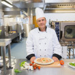 Chef standing in the kitchen with pizza — Stock Photo #23105212