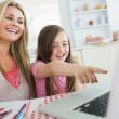 Little girl and mother laughing at laptop — Stock Photo